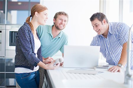 Young couple with salesman in kitchen showroom Stock Photo - Premium Royalty-Free, Code: 649-06844113