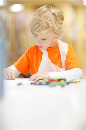 Boy concentrating on drawing Stock Photo - Premium Royalty-Free, Code: 649-06844152