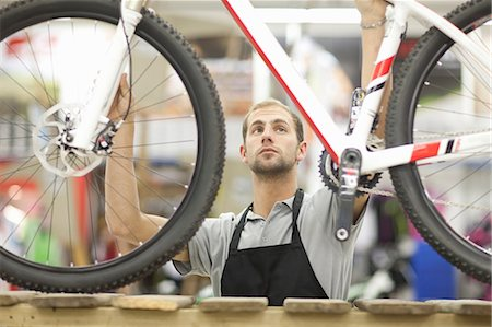 retail store - Young man holding bicycle in repair shop Stock Photo - Premium Royalty-Free, Code: 649-06844219