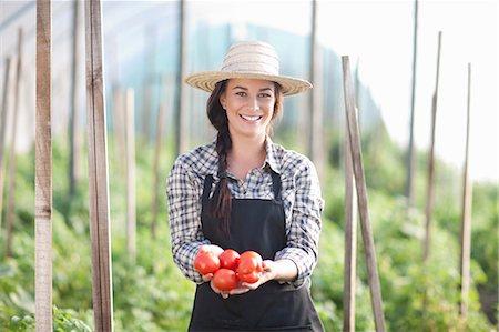 farmhand (female) - Woman holding tomatoes grown at farm Stock Photo - Premium Royalty-Free, Code: 649-06844246