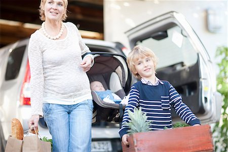 Mother with baby car seat and son carrying box of plants Stock Photo - Premium Royalty-Free, Code: 649-06844306