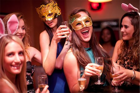 Young women with drinks wearing masks at hen party Stock Photo - Premium Royalty-Free, Code: 649-06844379