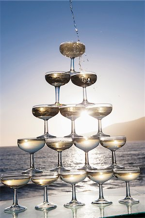 Champagne pouring into glasses with sea in background Stock Photo - Premium Royalty-Free, Code: 649-06844407