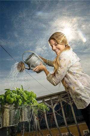 pouring - Young woman watering plants Stock Photo - Premium Royalty-Free, Code: 649-06844408