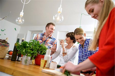 Mother with grown up children preparing food in kitchen Stock Photo - Premium Royalty-Free, Code: 649-06844450