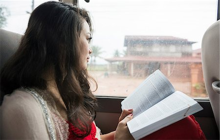 Woman looking out of window on bus with book Stock Photo - Premium Royalty-Free, Code: 649-06844461