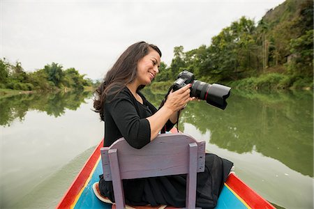 Woman with camera on boat on Nam Song River, Vang Vieng, Laos Stock Photo - Premium Royalty-Free, Code: 649-06844463