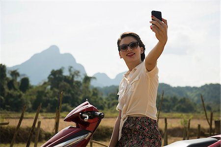 Woman photographing self on moped, Vang Vieng, Laos Stock Photo - Premium Royalty-Free, Code: 649-06844476