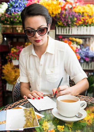 Woman writing postcard in cafe Stock Photo - Premium Royalty-Free, Code: 649-06844473