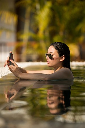 exotic outdoors - Woman using smartphone in  swimming pool Stock Photo - Premium Royalty-Free, Code: 649-06844485
