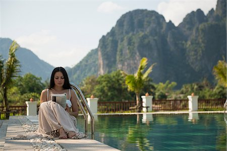 exotic outdoors - Woman sitting reading by swimming pool, Vang Vieng, Laos Stock Photo - Premium Royalty-Free, Code: 649-06844482