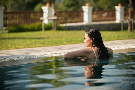 exotic outdoors - Woman leaning on edge of  swimming pool Stock Photo - Premium Royalty-Free, Code: 649-06844483