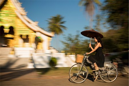 Woman riding bicycle with parasol, Luang Prabang, Laos Stock Photo - Premium Royalty-Free, Code: 649-06844498