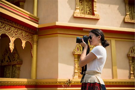 Woman taking photograph outside building, Luang Prabang, Laos Stock Photo - Premium Royalty-Free, Code: 649-06844501