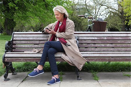 Senior woman sitting on park bench and looking at mobile phone Stock Photo - Premium Royalty-Free, Code: 649-06844540