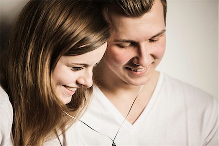 Teenage couple smiling and sharing earphones Stock Photo - Premium Royalty-Free, Code: 649-06844601