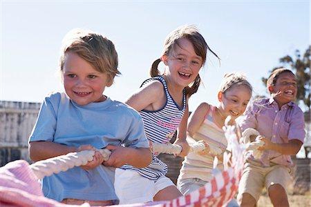 pulling - Four children playing tug of war Stock Photo - Premium Royalty-Free, Code: 649-06844642