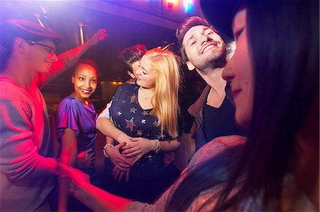Group of people at party, man kissing woman's neck Stock Photo - Premium Royalty-Free, Code: 649-06844728