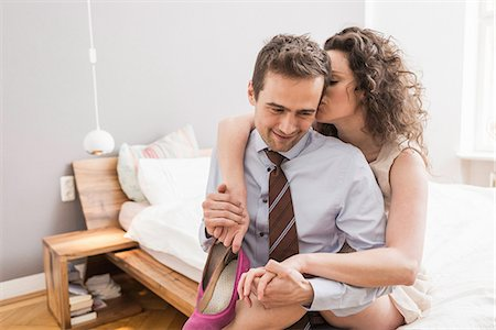 Mid adult couple face to face with arm around, smiling and holding shoe Stock Photo - Premium Royalty-Free, Code: 649-06844747