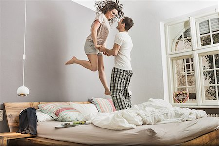 romantic couple bed - Mid adult couple wearing pyjamas jumping on bed Stock Photo - Premium Royalty-Free, Code: 649-06844748