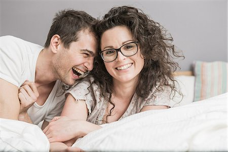 romantic couple bed - Mid adult woman couple fooling around on bed Stock Photo - Premium Royalty-Free, Code: 649-06844754