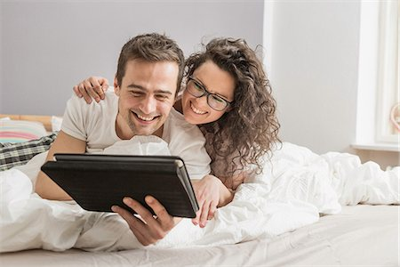romantic couple bed - Mid adult couple lying on bed using digital tablet Stock Photo - Premium Royalty-Free, Code: 649-06844759