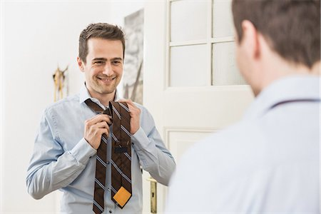 Mid adult man fastening tie in mirror Stock Photo - Premium Royalty-Free, Code: 649-06844764