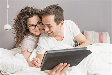 romantic couple bed - Mid adult couple lying on bed using digital tablet Stock Photo - Premium Royalty-Free, Code: 649-06844760