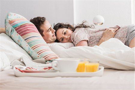 romantic couple bed - Mid adult couple lying in bed, breakfast on tray, hugging Stock Photo - Premium Royalty-Free, Code: 649-06844776