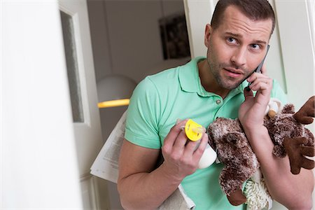 people in panic - Mid adult man holding cuddly toy and baby's pacifier Stock Photo - Premium Royalty-Free, Code: 649-06844855