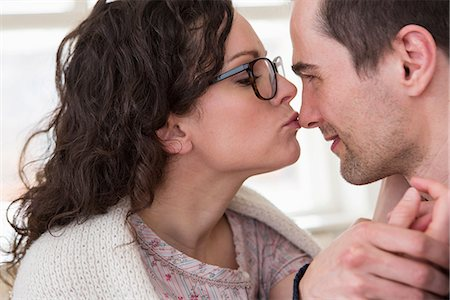 Mid adult woman giving man a kiss on the nose Stock Photo - Premium Royalty-Free, Code: 649-06844869
