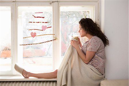 Mid adult woman sat on window seat Stock Photo - Premium Royalty-Free, Code: 649-06844878