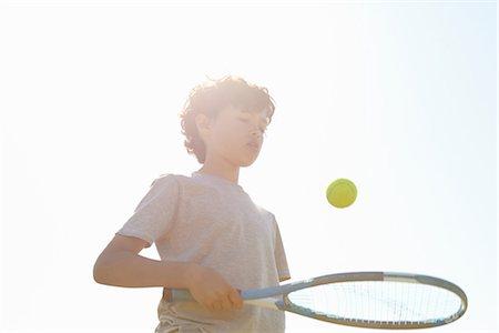preteen boys playing - Boy bouncing ball on tennis racket Stock Photo - Premium Royalty-Free, Code: 649-06844916
