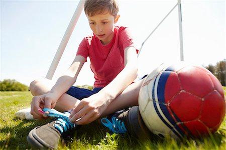 Boy sitting on field tying shoe lace Stock Photo - Premium Royalty-Free, Code: 649-06844913