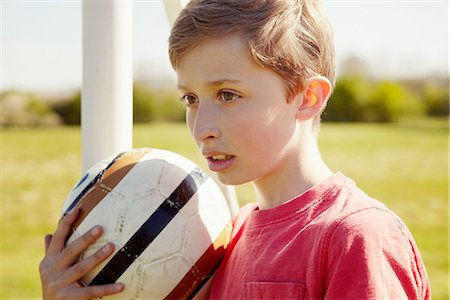 Boy with ball looking into the distance Stock Photo - Premium Royalty-Free, Code: 649-06844923