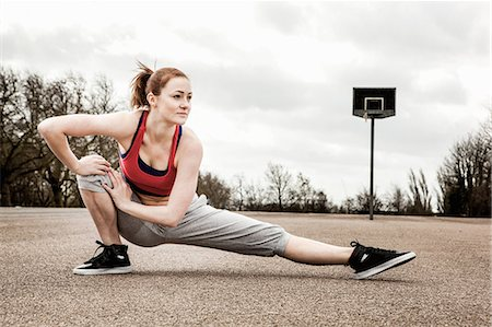 right - Woman stretching left leg and bending right leg on court Stock Photo - Premium Royalty-Free, Code: 649-06844931