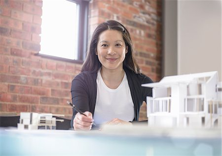 Architect working at desk in office with model of buildings Stock Photo - Premium Royalty-Free, Code: 649-06845032