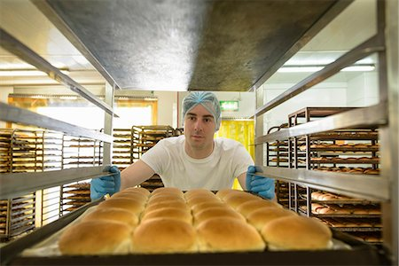 Baker organising trays of freshly baked bread Stock Photo - Premium Royalty-Free, Code: 649-06845107