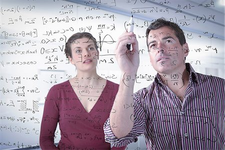 Mathematicians writing complex scientific equations on screen Stock Photo - Premium Royalty-Free, Code: 649-06845128