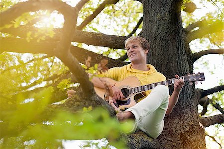 Portrait of young man sitting in tree with guitar Stock Photo - Premium Royalty-Free, Code: 649-06845146