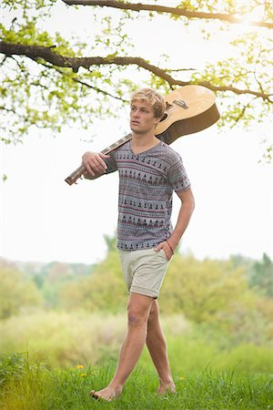 Young man walking through field with guitar Stock Photo - Premium Royalty-Free, Code: 649-06845148
