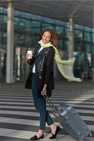 pulling - Young woman at airport with wheeled case and coffee Stock Photo - Premium Royalty-Free, Code: 649-06845158