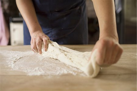 Close up of hands stretching bread dough Stock Photo - Premium Royalty-Free, Code: 649-06845218
