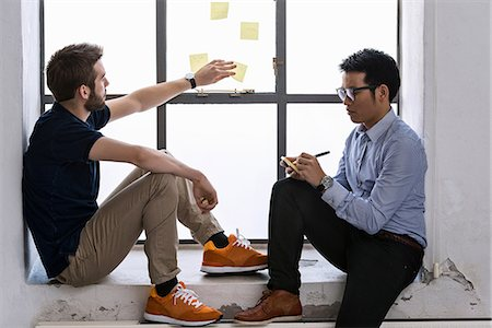 Two young male designers sharing ideas on post it notes Stock Photo - Premium Royalty-Free, Code: 649-06845210