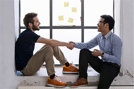 designer - Two young male creatives shaking hands Stock Photo - Premium Royalty-Free, Code: 649-06845212