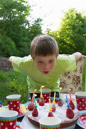 summer - Close up portrait of young boy blowing out birthday candles Stock Photo - Premium Royalty-Free, Code: 649-06845266