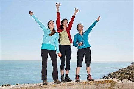 Three female friends waving from wall at coast Stock Photo - Premium Royalty-Free, Code: 649-06845284