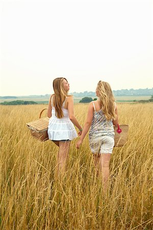 Two girls in a field with picnic baskets Stock Photo - Premium Royalty-Free, Code: 649-06843984