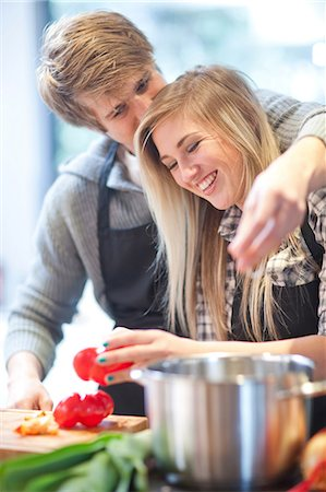 Affectionate young couple preparing meal Stock Photo - Premium Royalty-Free, Code: 649-07064025