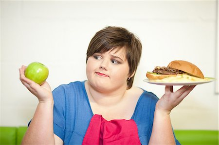fat lady sitting - Young woman choosing between an apple and a burger Stock Photo - Premium Royalty-Free, Code: 649-07064044